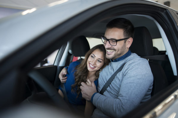Happy young couple enjoying their brand new car.