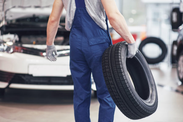 Mechanic holding a tire tire at the repair garage. replacement of winter and summer tires